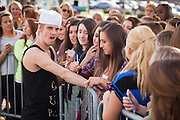 Madison Weisbarth writes her name, number, and a heart on Aaron Carter's arm before his concert in the South Green at Ohio University on April 24, 2014.  Photo by Ohio University / Jonathan Adams