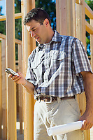 Young male contractor at construction site using mobile phone.