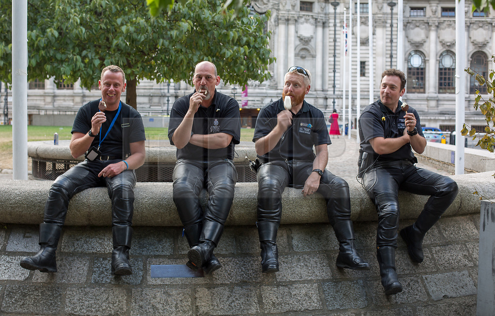 @Licensed to London News Pictures 13/07/2018. London, UK. Members of the Metroplolitan Police  Special Escort Group in London cooling off with ice lollies after demonstrators march through the streets of Central London arriving at Trafalgar Square in protest to the US President Donald Trump' visit to the UK.Photo credit: Manu Palomeque/LNP