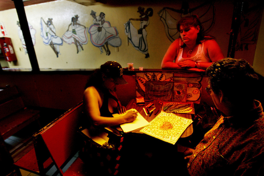 TIJUANA, MEXICO:  An artist draws pictures in a dance bar in Tijuana, Mexico