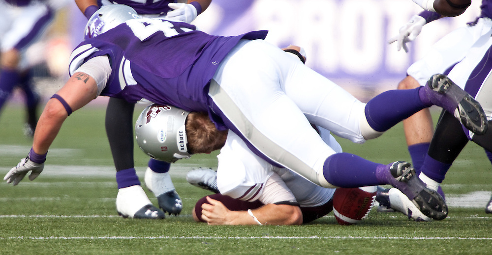 London, ONT.; September 17, 2011 -- Ottawa quarterback Aaron Colbon has his helmet knocked off as he is hit by Western's Brent Wheeler during the Gee Gee's 41- 13 loss to the Western Mustangs at TD Waterhouse Stadium in London, Ontario, September 17, 2011.  <br /> <br /> (GEOFF ROBINS/ Ottawa Citizen)