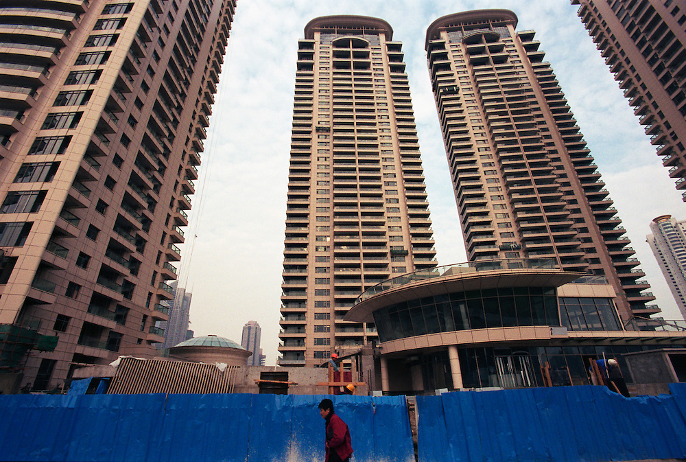 Luxury apartment buildings sprouting in the new Pudong financial district of Shanghai. As China's economy continues to boom, more and more chinese are obtaining the modern energy consuming amenities that wealth and improved living standards bring. China's soaring demand for energy is having serious effects on the environment. 75% of China's energy needs is supplied by coal, the cheapest and dirtiest form of energy, and seven of the world's ten most polluted cities are in China...Shanghai, China. 19/11/2005..Photo © J.B. Russell