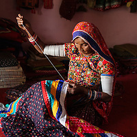 Experienced embroiderer in Bhuj area of Gujarat stitching finishing touches on an elaborate quilt