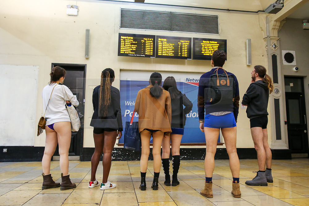 """© Licensed to London News Pictures. 13/01/2019. London, UK. Participants take part in 10th anniversary of 'No Trousers Tube Ride' by viewing the information board at Paddington Station. The """"No Pants Subway Ride"""" is an annual event staged by Improve Everywhere every January in New York City. The mission started as a small prank with seven guys and has grown into an international celebration of silliness, with dozens of cities including London around the world participating each year. Photo credit: Dinendra Haria/LNP"""