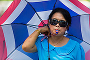 16 MAY 2014 - BANGKOK, THAILAND: An anti-government protestor with an umbrella in the Thai colors stands in front of the Thai parliament complex. Thousands of protestors from the People's Democratic Reform Committee (PDRC) surrounded the Thai Parliament complex Saturday to pressure the Thai Senate to select an interim Prime Minister to replace ousted former PM Yingluck Shinawatra. The Senate decided not to appoint an interim PM of their own and announced a meeting with the current interim Prime Minister. The protestors left the parliament complex and threatened to return in larger numbers if the Senate doesn't act. The Senate appointment of an acting PM could plunge Thailand into chaos since there is already an interim Prime Minister from the ruling Pheu Thai party.     PHOTO BY JACK KURTZ
