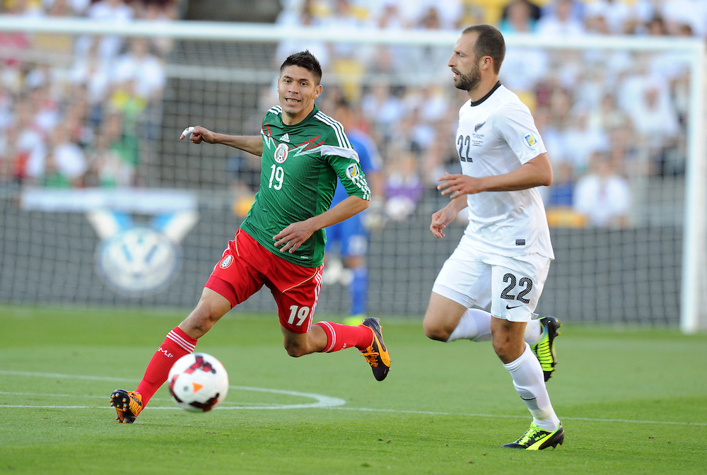 Mexico's Oribe Peralta, left, plays in front of New Zealand's Andrew Durante fin the World Cup Football qualifier, Westpac Stadium, Wellington, New Zealand, Wednesday, November 20, 2013. Credit:SNPA / Ross Setford