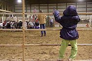 Kaia Heitkamp (on fence,) from Lebanon, watches the cowboy prayer, before the rodeo at Fox Hollow Stables in Waynesville, Saturday, March 3rd.