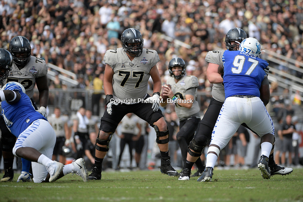 Central Florida offensive lineman Jake Brown (77) sets up to block during the first half of the American Athletic Conference championship NCAA college football game against Memphis Saturday, Dec. 2, 2017, in Orlando, Fla. (Photo by Phelan M. Ebenhack)
