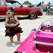 One year old Maritza Cordova stands next to a toy car customized by her father, Larry Cordova, on the lot of the Classic Car Show during the Mex-Tex Family Fiesta event at the Scharbaur Sports Complex in Midland, TX.