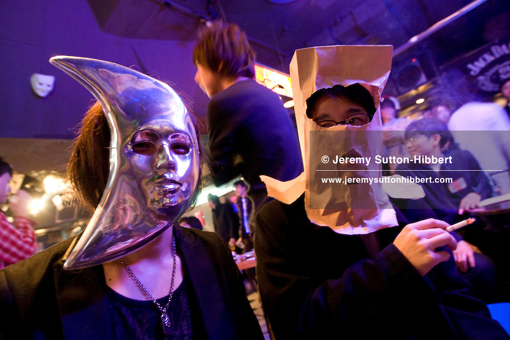 A participant wears a mask to protect his identity, and to shield his shyness, in the 'Himote Valentine' event held in the early hours of St. Valentine's Day, at Loft/Plus One in Shinjuku, Tokyo, Japan, Saturday 14th February 2009. The event, attended by approximately 100 people, was billed as an opportunity for 'lonely people to be in the company of other lonely people', to have a drink and to relax.  The event was organised by Hiroyuki Egami, founder of 'Himote SNS' - a networking website, with 15,000 members, for those who are uninterested in relationships, or those who are shy and have difficulty communicating with others.