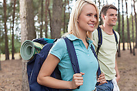 Beautiful young backpacker with man trekking in forest
