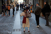A girl dressed up with traditional basque clothes and playing the accordion in the streets of Getaria.