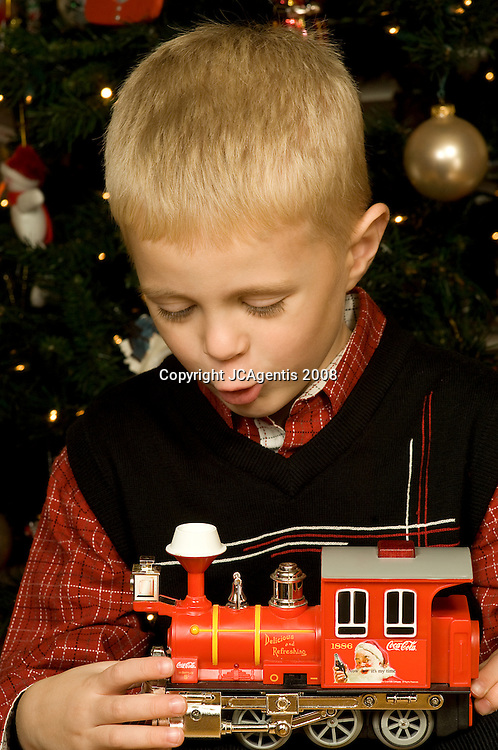 Young boy delighted with his Christmas present, a toy train.  Lexington, KY 01/02/2008
