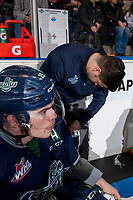 KELOWNA, CANADA - FEBRUARY 23: Donovan Neuls #19 of the Seattle Thunderbirds sits on the bench as equipment manager Trevor Heinzerling laces his skates against the Kelowna Rockets on February 23, 2018 at Prospera Place in Kelowna, British Columbia, Canada.  (Photo by Marissa Baecker/Shoot the Breeze)  *** Local Caption ***