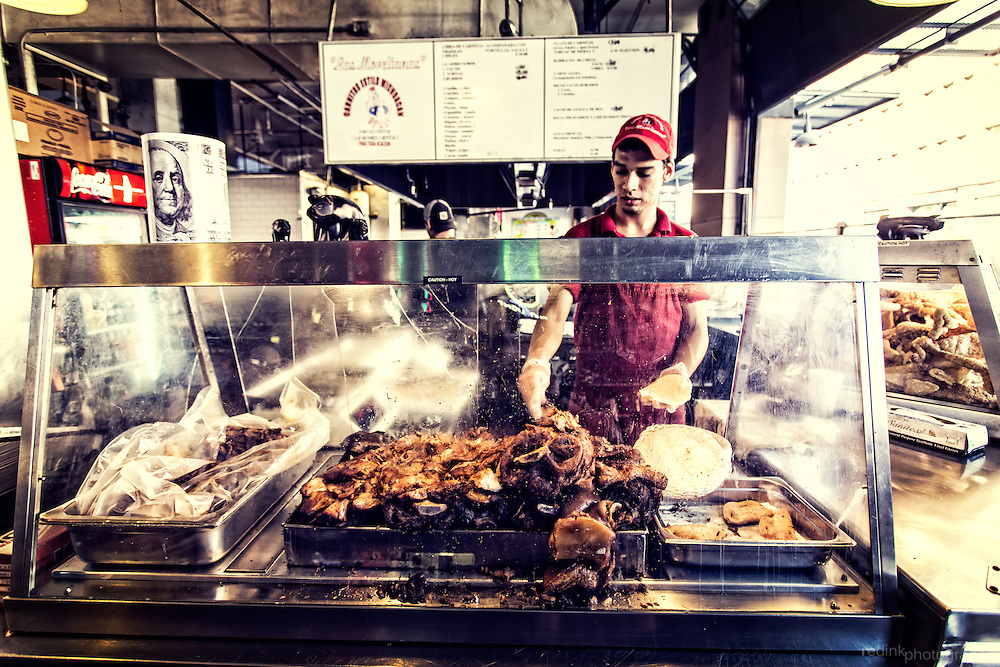 Workers makes pork carnitas taco at a stand in the Grand Central Market. Downtown Los Angeles, California. PS...it was quite good.