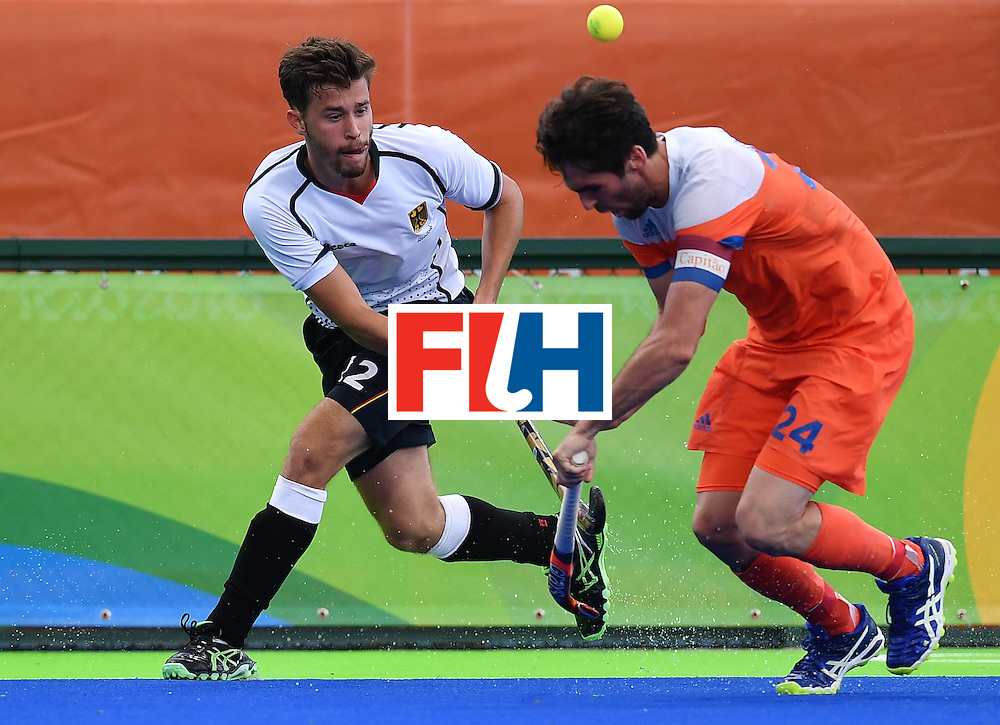 Germany's Timm Herzbruch (L) vies with Netherlands' Robert van der Horst during the mens's field hockey Germany vs Netherlands match of the Rio 2016 Olympics Games at the Olympic Hockey Centre in Rio de Janeiro on August, 12 2016. / AFP / MANAN VATSYAYANA        (Photo credit should read MANAN VATSYAYANA/AFP/Getty Images)