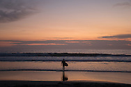 Beautiful pink sunset with a sufer walking into  the waves at the Santa Monica beach. Santa Monica, CA 1.9.15