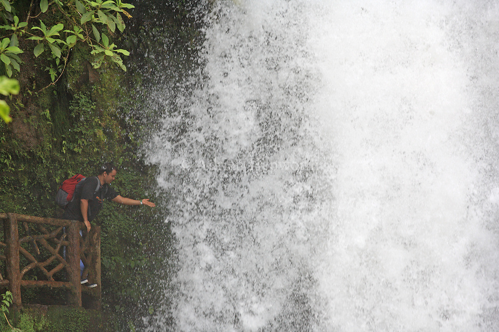 Tourist at waterfall of R&iacute;o Paz in La Paz Waterfall Gardens / Peace Lodge,.Near Vara Blanca, Costa Rica.<br />