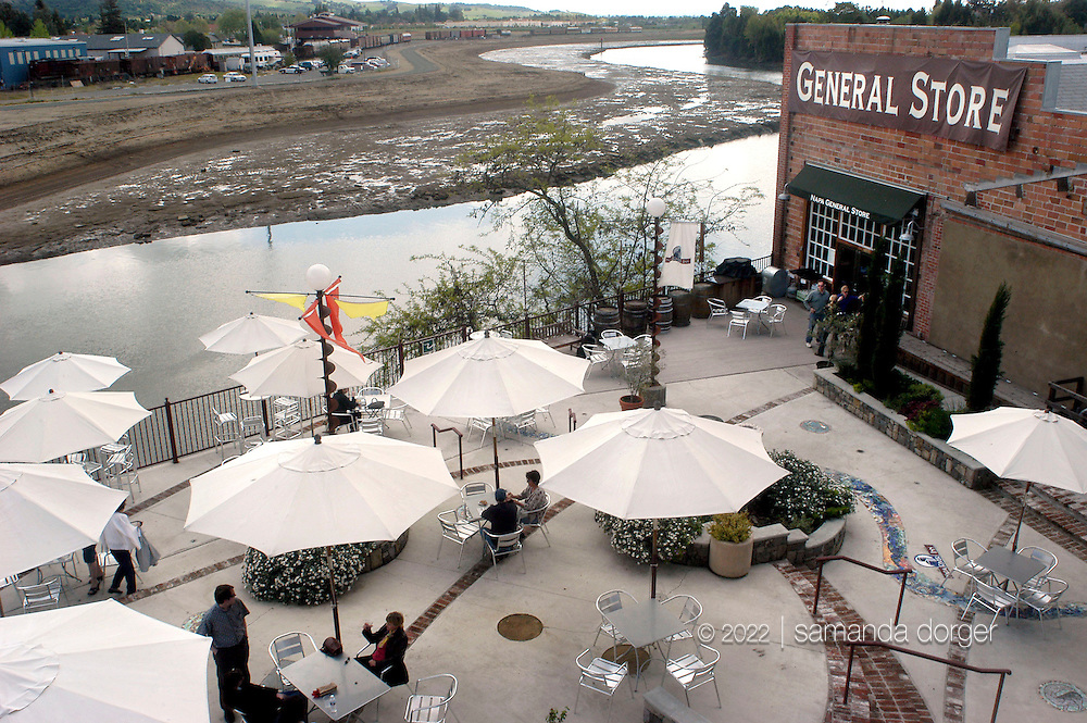 "Redevelopment along the Napa River includes a hotel, restaurants and shops in the historic Hatt building in downtown Napa as seen in this March 27, 2004 photo.  Riverbank terracing, which provides room for excess water, can be seen on the opposite bank of the river at lowtide, with the second terrace unflooded. The terraces flood during high tide, and provide wetlands in low tide. Napa's unique ""Living River"" flood control project allows water to flow in its historical channel, creating wetlands, restoring the life of the river, and protecting property from floods."