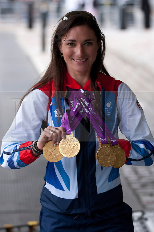 © Licensed to London News Pictures. 10/09/2012. LONDON, UK. Paralympic medal winning cyclist Sarah Storey holds up her four gold medals as she arrives at a reception for British Olympic and Paralymic athletes held at the Queen Elizabeth II Conference Centre in London today (10/09/12). Photo credit: Matt Cetti-Roberts/LNP