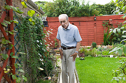 © Licensed to London News Pictures. 09/04/2014<br /> <br /> Durham, United Kingdom<br /> <br /> Parkinson's Disease sufferer David Forsyth from Brandon, County Durham walks around his garden at his home. A keen gardner it is becoming increasingly more difficult to carry out some of the most basic tasks in the garden.<br /> <br /> Parkinson's is a long-term neurological condition that affects the way the brain co-ordinates body movements including walking, talking and writing and affects both men and women.<br /> <br /> Photo credit : Ian Forsyth/LNP