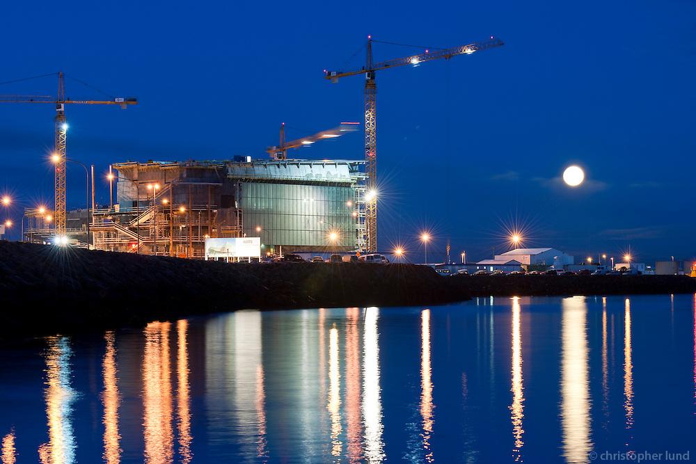 """Tónlistarhúsið Harpa í byggingu. Ljósaskiptin, fullt tungl á himni. The Icelandic National Concert and Conference Centre """"Harpa"""" under construction. Twilight and full moon."""