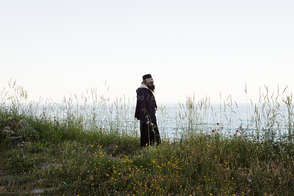 MOUNT ATHOS, GREECE - 7 MAY 2014: Father Joachim, one of the monks living in Mylopotamos, watches the bay and Mount Athos at dusk from the Mylopotamos skete in the Mount Athos peninsula, Greece, on May 7th 2014.<br /> <br /> A skete is a community of Christian hermits following a monastic rule, and depending from one of the 20 monasteries ruling Mount Athos. Mylopotamos, famous for its wine and the cuisine of chef monk Father Epiphanios, is the largest dependency of the Holy Monastery of Great Lavras.<br /> <br /> Mount Athos is a mountain and peninsula in Greece. A World Heritage Site and autonomous polity in the Hellenic Republic, Athos is home to 20 stavropegial Eastern Orthodox monasteries under the direct jurisdiction of the patriarch of Constantinople. Greeks commonly refer to Mount Athos as the &quot;Holy Mountain&quot;.<br /> <br /> Mount Athos is a mountain and peninsula in Greece. A World Heritage Site and autonomous polity in the Hellenic Republic, Athos is home to 20 stavropegial Eastern Orthodox monasteries under the direct jurisdiction of the patriarch of Constantinople. Greeks commonly refer to Mount Athos as the &quot;Holy Mountain&quot;.