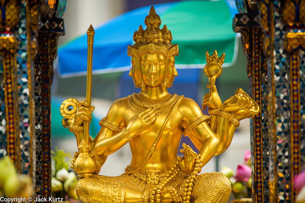 27 SEPTEMBER 2012 - BANGKOK, THAILAND: The Phra Phrom at the Erawan Shrine in Bangkok. The Erawan Shrine is a Hindu shrine in Bangkok, Thailand, that houses a statue of Phra Phrom, the Thai representation of the Hindu creation god Brahma. A popular tourist attraction, it often features performances by resident Thai dance troupes, who are hired by worshippers in return for seeing their prayers at the shrine answered. The Erawan Shrine was built in 1956 as part of the government-owned Erawan Hotel to eliminate the bad karma believed caused by laying the foundations on the wrong date. The hotel's construction was delayed by a series of mishaps, including cost overruns, injuries to laborers, and the loss of a shipload of Italian marble intended for the building. Furthermore, the Ratchaprasong Intersection had once been used to put criminals on public display. An astrologer advised building the shrine to counter the negative influences. The Brahma statue was designed and built by the Department of Fine Arts and enshrined on 9 November 1956. The hotel's construction thereafter proceeded without further incident. In 1987, the hotel was demolished and the site used for the Grand Hyatt Erawan Hotel.     PHOTO BY JACK KURTZ