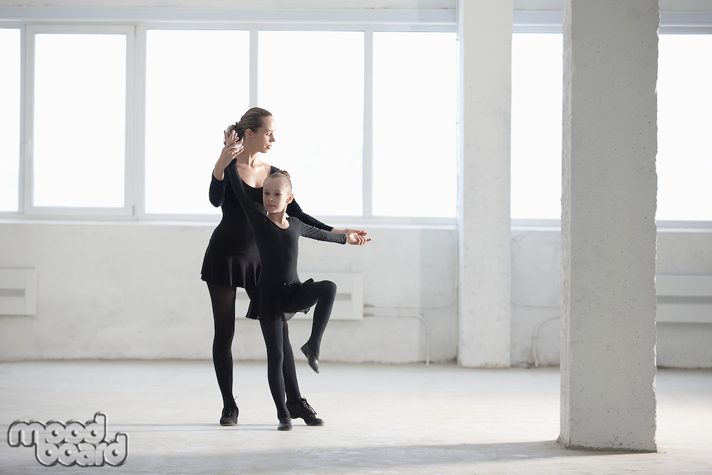 Woman and girl practise dance moves