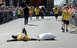 © Licensed to London News Pictures. 06/04/2015. Gawthorpe, UK. Competitor John Gibbons falls as he approaches the finish line during the World Coal Carrying Championships, Gawthorpe, West Yorkshire. Photo credit : Anna Gowthorpe/LNP