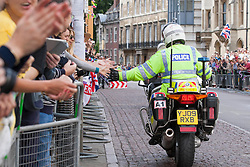 Image &copy;Licensed to i-Images Picture Agency. 07/07/2014. Cambridge, United Kingdom. Tour de France Stage 3 Cambridge. Motorcycle cop slaps hands en-route<br /> Cambridge, City Centre. Picture by Terry Harris / i-Images