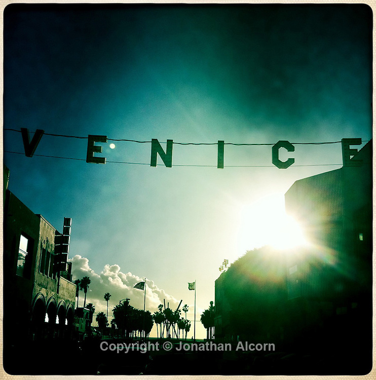 The sun sets behind the Venice Beach sign at Windward and Pacific . hipstamatic print