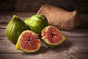 Old style still life with ripe fresh figs on wooden table.