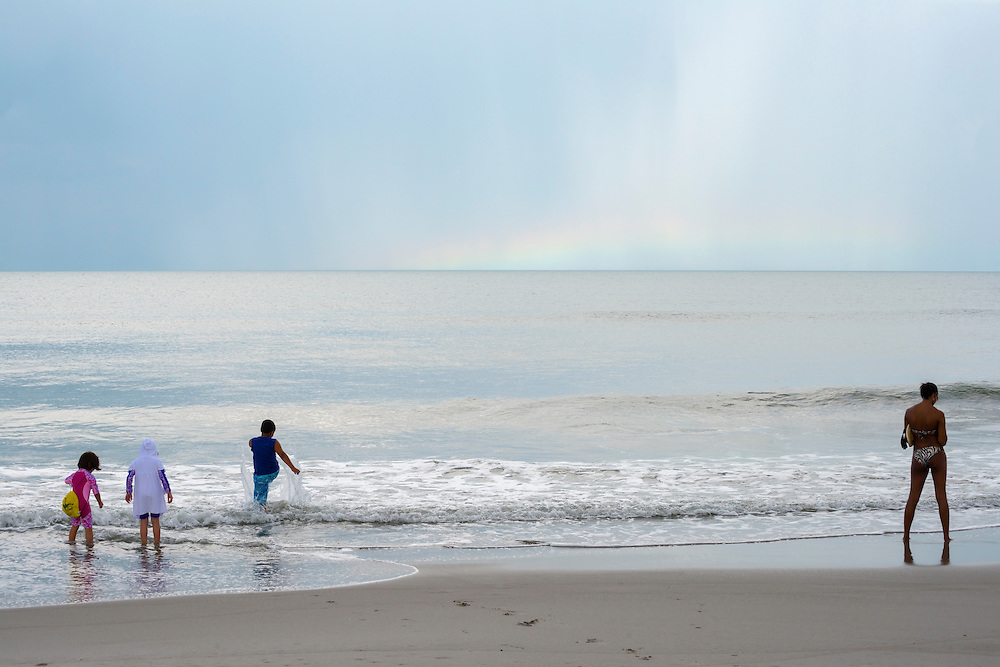 A Delta flight attendant on an overnight layover and three kids enjoy an evening at the beach in Indialantic, Florida. A rainbow is stretched low on the horizon.