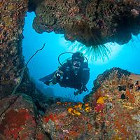 Diver exploring cave, Tenggol Island, Tanjong Jara Resort, Terengganu, Malaysia.