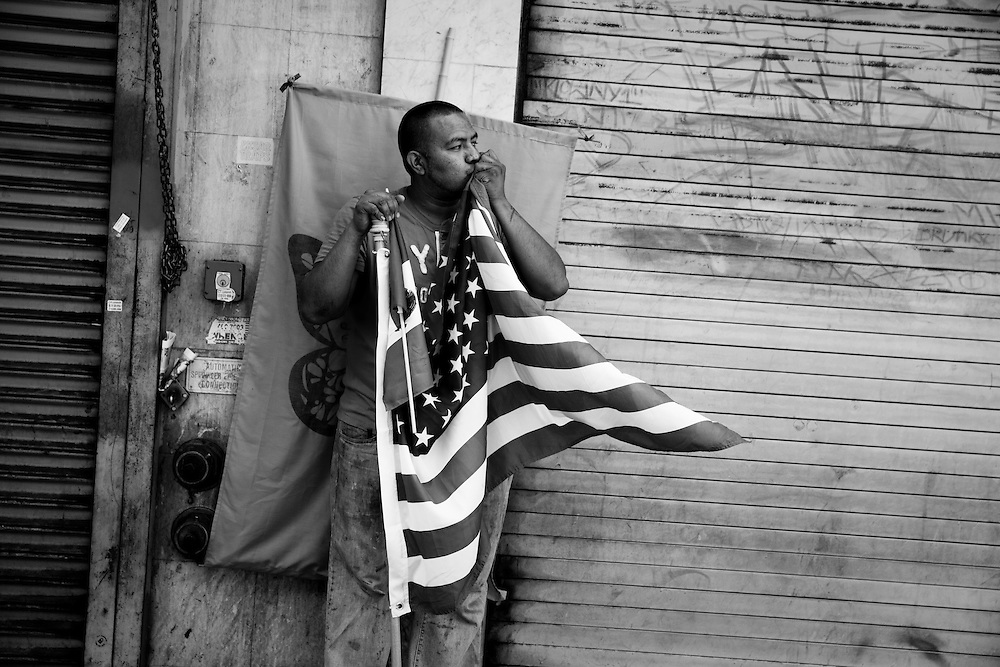 A man kisses the American flag while watching immigrant rights supporters march in Los Angeles. Photographed for Aurora Photos. Please contact Todd Bigelow directly with your licensing requests.