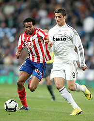 MADRID, SPAIN - Sunday, March 28, 2010: Real Madrid Club de Futbol's Christiano Ronaldo in action against Club Atletico de Madrid's Paulo Assuncao during the La Liga Primera Division Madrid Derby match at the Estadio Santiago Bernabeu. (Pic by Hoch Zwei/Sprimont Press/Propaganda)