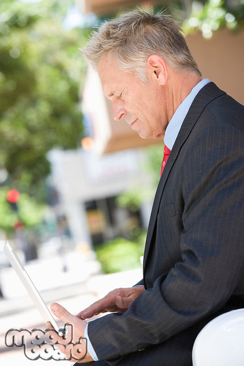 Middle-aged businessman using laptop outdoor