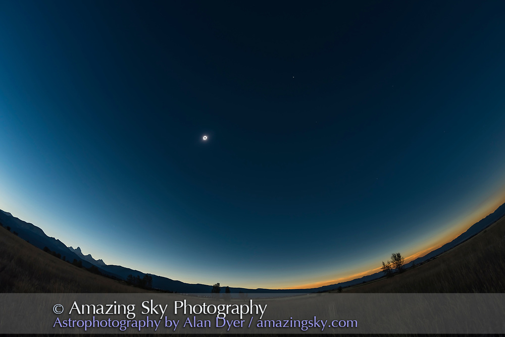 An ultra-wide angle view of the total eclipse sky from the Teton Valley, Idaho. The Tetons are at left, still partly in sunlight. The lunar shadow has approached from the west at right and its edge is just past the Sun, ending the diamond ring and starting totality. Venus is at upper right from the Sun. Sirius is a tiny speck at lower right, likely not visible in low-res views on social media. Procyon, Rigel, and Betelegeuse are faintly visible in the original image. <br /> <br /> The horizon had colours mostly to the south. <br /> <br /> This is a single frame from a 660-frame time-lapse of the motion of the lunar shadow, taken with the Nikon D750 and 12mm full-frame Rokinon fish-eye lens.