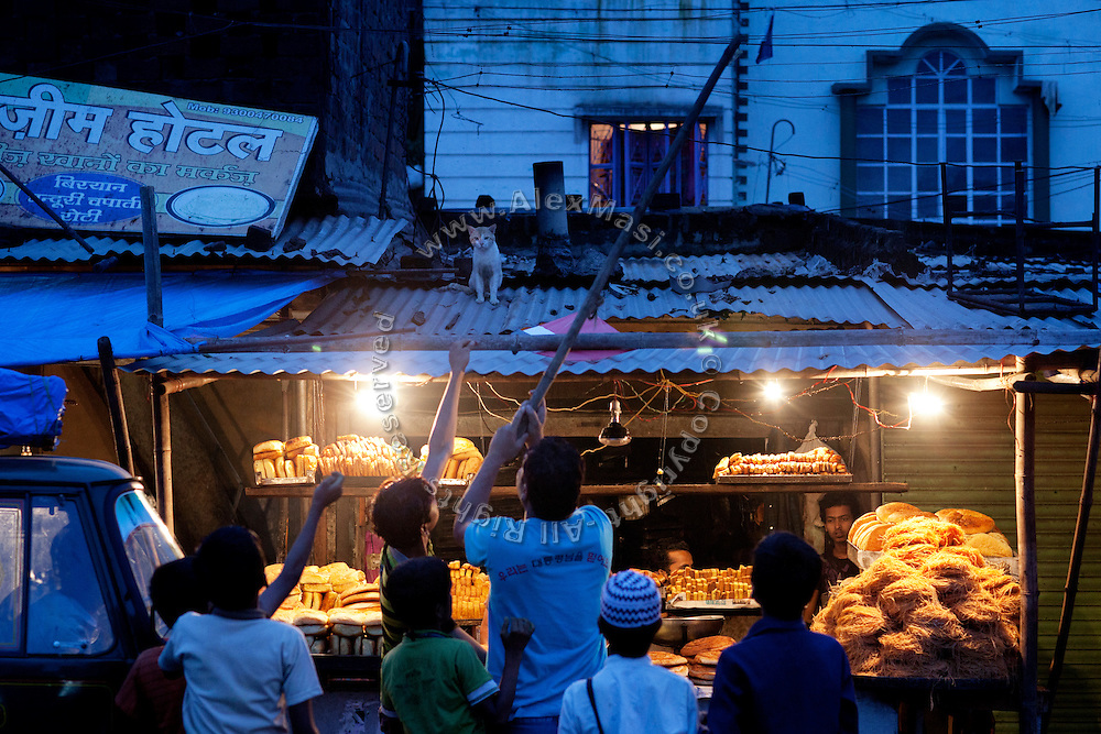 During the holy month of Ramadan, a group of boys with a stick are trying to force a stray cat to move away from the rugged metal root of a stall selling bread and sweets in Kasi Camp, one of the nineteen water-affected colonies surrounding the abandoned Union Carbide (now DOW Chemical) industrial complex in Bhopal, Madhya Pradesh, India.