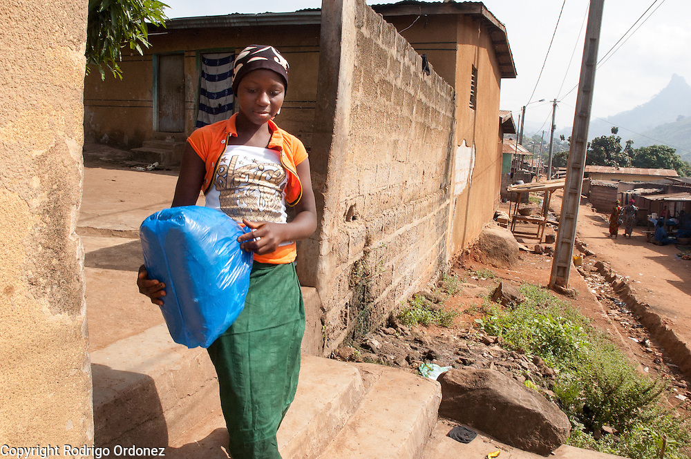 Maimouna, 11, leaves the home of family friends in Man, western C&ocirc;te d'Ivoire, the morning before being reunited with her family. She is carrying a plastic bag with her belongings. <br /> Maimouna had been separated from her family for three months, since the moment armed conflict broke out in her hometown, Du&eacute;kou&eacute;, and she had to flee to Man. Save the Children facilitated the reunion with her parents and her return home.