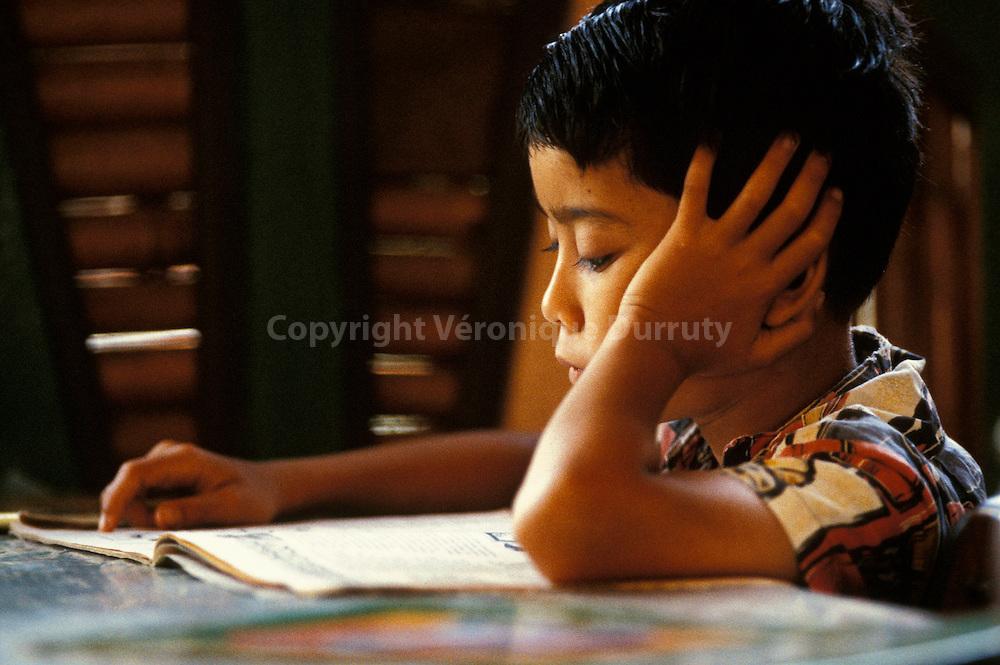 ENFANT EN TRAIN DE LIRE, SUMATRA, INDONESIE