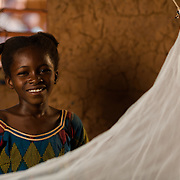 Rasmata Ouedraogo (11) with her mosquito net in the village of Bore in the Sanmatenga region of Burkina Faso on 24 February 2014. Mosquito nets greatly decrease the incidence of malaria by reducing the risk of being bitten by the nocturnal Anopheles mosquito, which carries the malaria parasite.
