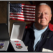 Bud Sweetman poses for a portrait with the Purple Heart and Bronze Star he recieved for serving in World War II. Sweetman, who will have dontaed 300 pints of blood began donating when he was discharged from the Army after spending 13 and a half months in the hospital for an injury he sustained in Vire, France in 1944.  (Jason A. Frizzelle) This collection of images illustrates a variety of portraits from headshots to location portraits. This collection of images represents more than a decade of work at newspapers and wire services throughout North Carolina. I now practice my style of story-telling photography for weddings community events as well as portrait sessions ranging from brides to local authors. After graduating from Randolph Community College I spent more than a decade documenting communities throughout Eastern North Carolina with a camera. My passion for capturing story-telling images has allowed me to witness everything from High School Football to Hurricanes and even Presidential visits.<br />