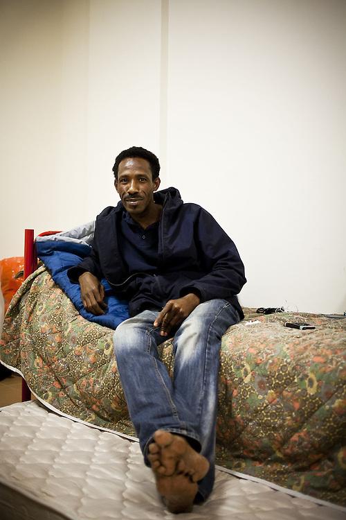 Ritratto di migrante sul letto. Interno ex palazzine olimpiche.
