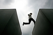 GERMANY - BERLIN - A tourist jumps from one block to the other on the Holocaust Monument .  PHOTO GERRIT DE HEUS
