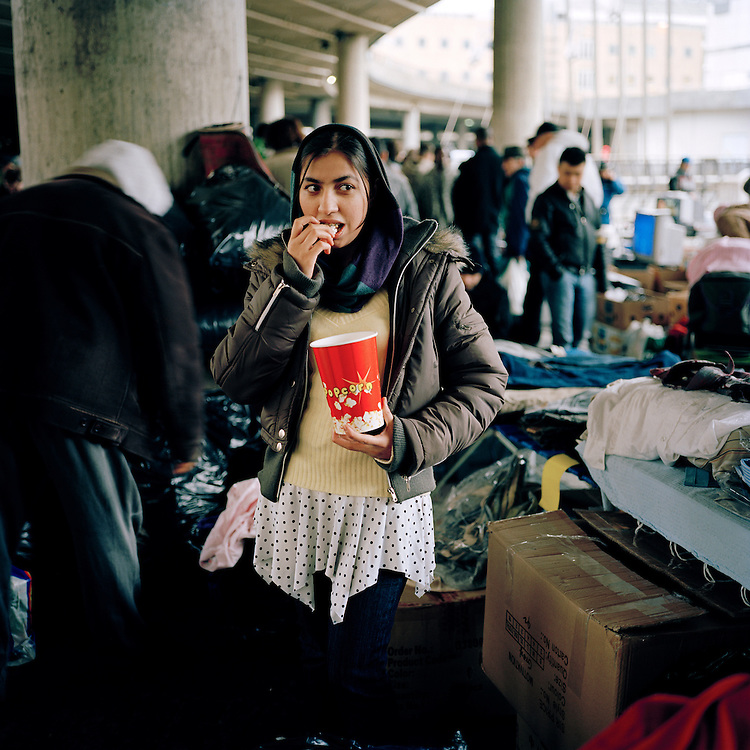 Afghan girl eating popcorn at the Saturday market at Groenland, Oslo, Norway. . ..Photo by Knut Egil Wang /MOMENT