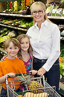 Portrait of a happy woman with grandchildren standing in farmer's market