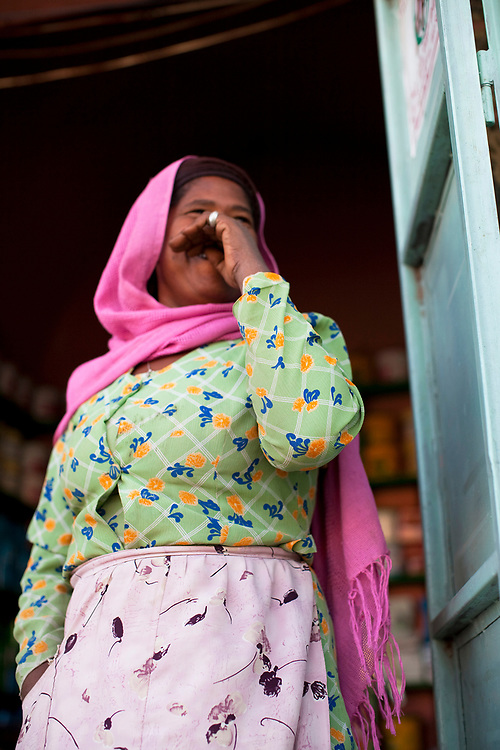Peasant woman dressed in bright chiffon in a doorway, Mekelle, Ethiopia