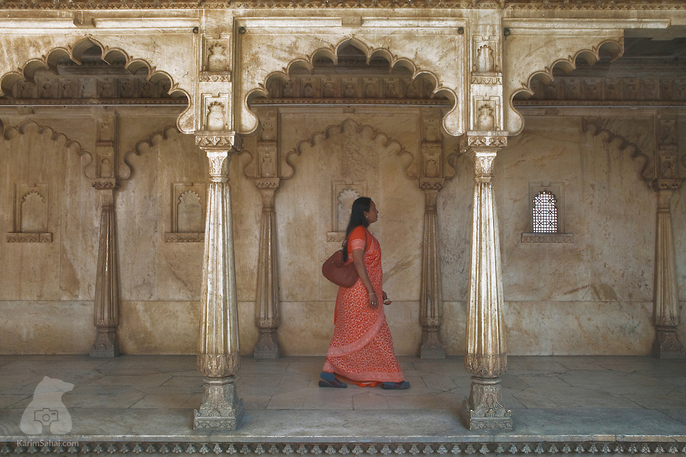 A woman walks under ornate arches at the City Palace in Udaipur, Rajasthan, India.